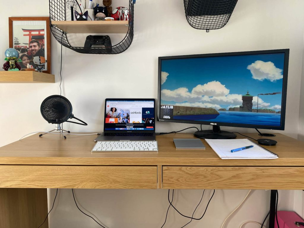Desk with laptop, microphone and second screen