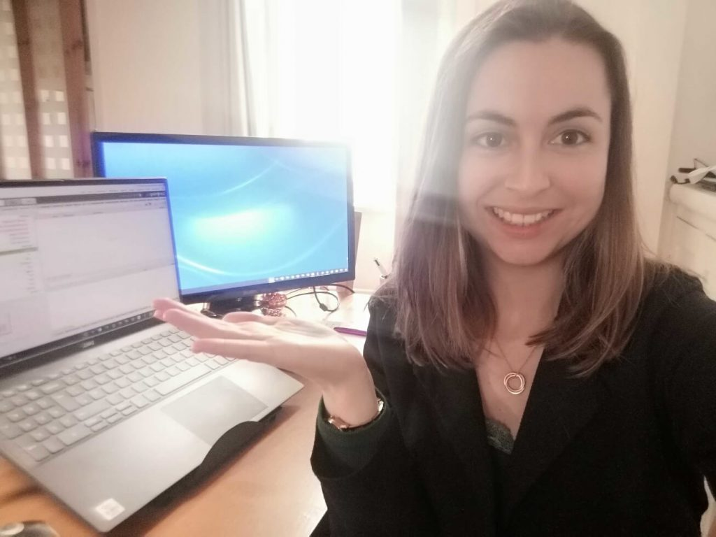 Xenia in front of her desk with laptop and second screen