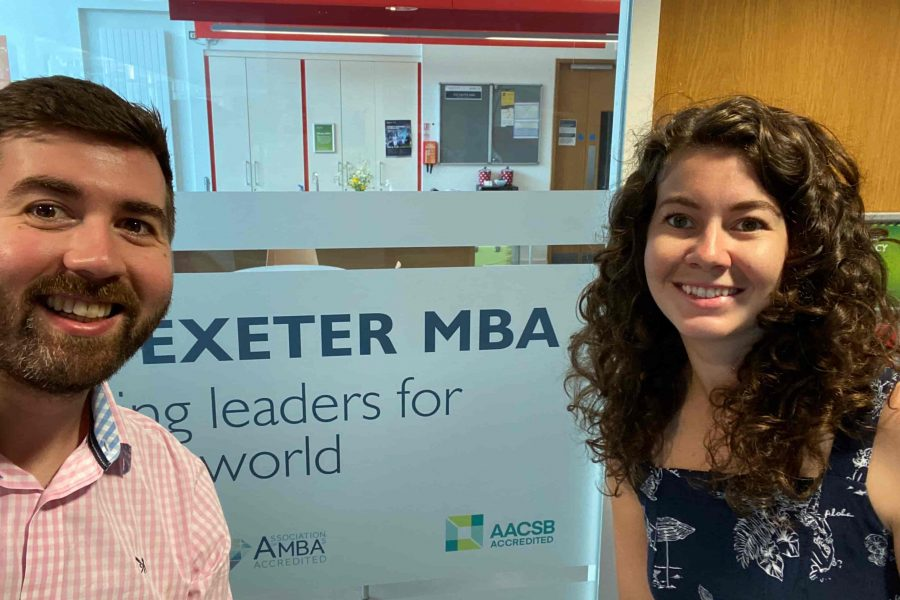 Jack and Becky in front of Exeter MBA sign at the University of Exeter